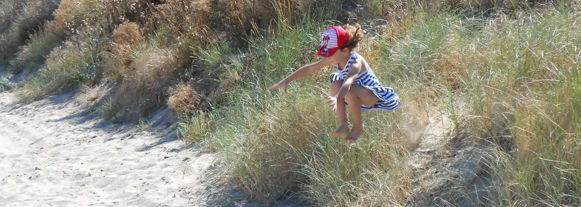 Kind springt in de zandduinen van Boyardville
